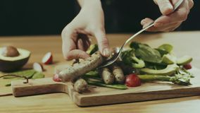 Hinzufügen von sousages auf Salaten stock video footage