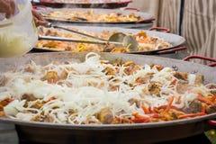 Hinzufügen von Zwiebeln einer riesigen Paella, gekocht in den enormen Wannen Lizenzfreies Stockbild