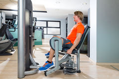 Hip abduction blond man exercise at gym indoor. Opening legs workout Royalty Free Stock Photography