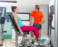Hip abduction woman exercise at gym closing. Hip abduction women exercise at gym indoor closing legs and personal trainer blond man Stock Image