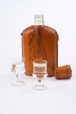 Hip flask and two glasses. Hip flask with leather cover and two glasses with alcohol, isolated on white Royalty Free Stock Images