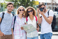 Hip friends holding map and taking picture at the camera Stock Photography