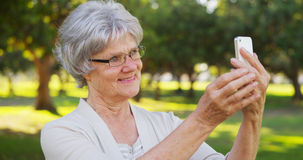 Hip grandma taking selfies at the park Stock Photography