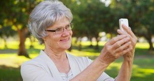 Hip grandma taking selfies at the park Stock Photography