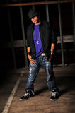 Hip Hop Artist Standing. African American hip hop dancer standing over industrial background Royalty Free Stock Photo