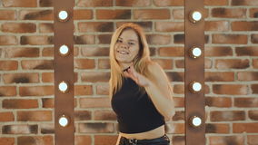 Hip hop blonde girl dancing in modern style over urban brick wall. Slow motion. Hip hop girl dancing in modern style over urban blue brick wall Girl in a black stock footage