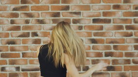 Hip hop blonde girl dancing in modern style over urban brick wall. Slow motion. stock video footage