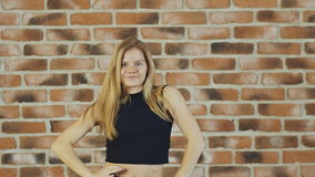 Hip hop blonde girl dancing in modern style over urban brick wall. Slow motion. Hip hop girl dancing in modern style over urban blue brick wall Girl in a black stock video footage
