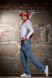 Hip hop boy dancing in modern style over brick wal Stock Photography