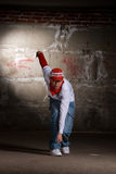 Hip hop boy dancing in modern style over grey wall Stock Photos