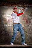 Hip hop boy dancing in modern style over grey wall Stock Images