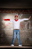 Hip hop boy dancing in modern style over grey wall Stock Photo