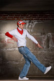 Hip hop boy dancing in modern style over grey wall Royalty Free Stock Photo