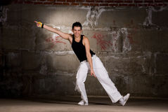 Hip hop boy dancing in modern style over grey wall Royalty Free Stock Photography