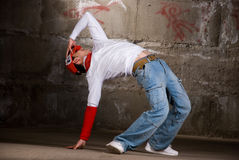 Hip hop boy dancing in modern style over grey wall Stock Photography