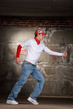 Hip hop boy dancing in modern style over grey wall Royalty Free Stock Photos
