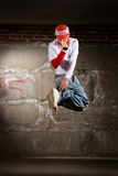 Hip hop boy dancing in modern style over grey wall Royalty Free Stock Image