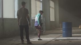 Hip hop culture. Rehearsal. Contemporary. Dance battle of two street dancers in an abandoned building near the barrel. stock footage