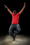 Hip Hop Dancer. African American hip hop dancer performing over dark background with spotlight royalty free stock image