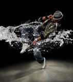 Hip Hop Dancer. African American dancer dancing with water splash over dark background Stock Photos