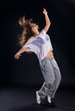 Hip-hop dancer. Girl dancing hip-hop on black background Stock Image