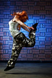Hip hop dancer. Hip hop girl dancing in modern style over urban blue brick wall Royalty Free Stock Photo