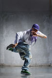 Hip-hop dancer. Cool looking hip-hop dancer posing on old wall royalty free stock images