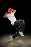 Hip Hop Dancer Dancing. African American hip hop dancer performing over dark background Royalty Free Stock Images