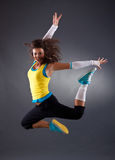 Hip hop dancer jumping. Beautiful young hip hop dancer jumping in studio stock image