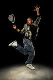 Hip Hop Dancer Jumping. African American hip hop dancer performing with hat over dark background with spotlight Stock Image