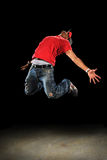 Hip Hop Dancer Jumping. African American hip hop dancer jumping over dark background royalty free stock photo