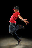 Hip Hop Dancer Performing. African American hip hop dancer performing over dark background with spotlight Stock Image