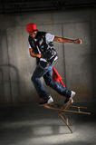 Hip Hop Dancer Performing. Falling on chair over industrial background Stock Images