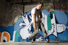 Hip hop dancer performing dance moves. In front of graffiti wall Stock Photo