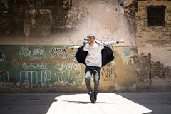 Hip hop dancer performing outdoors. Full length portrait of a handsome hip hop dancer freestyling outdoors in an abandoned building stock image