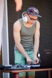Hip-hop DJ com os fones de ouvido na cabeça atrás do controlo a distância imagens de stock royalty free
