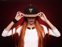 Hip-hop girl in cap with long red hair Royalty Free Stock Photos