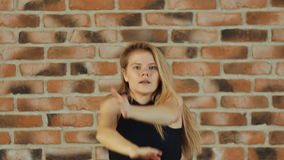 Hip hop girl dancing in modern style over urban brick wall. Hip hop girl dancing in modern style over urban blue brick wall Girl in a black T-shirt. Shot in Full stock footage