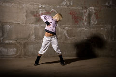 Hip hop girl dancing over grey brick wal Royalty Free Stock Photos