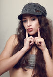 Hip-hop girl in hat posing and showing kissing Stock Images
