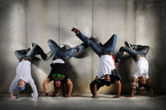 Hip Hop Men on Handstand. Hip Hop men performing dance with handstand over grunge background Royalty Free Stock Photography