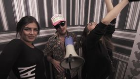 Hip hop musician with girls dancing and rapping into megaphone. Hip hop caucasian tattooed musician in sunglasses with girls in black dresses dancing and rapping stock video