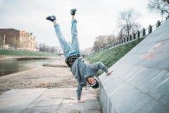Hip hop performer, upside down motion on street. Hip hop performer, upside down motion on the street. Modern dance style. Male dancer Royalty Free Stock Image