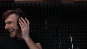 Hip-hop piosenkarz w hełmofonów śmiać się Chłopiec ono uśmiecha się i śpiewa w domowym wokalnie studiu zbiory