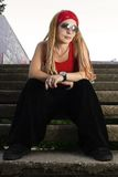 Hip-hop styled girl in red posing. Young hipster girl with braids posing outdoors Stock Images