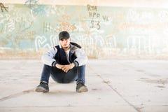 Hip-Hop-Tänzer, der draußen sitzt Lizenzfreie Stockfotos