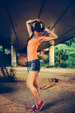 Hip hop woman with a cap which and headphones listenin Royalty Free Stock Photos