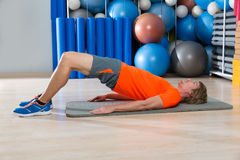 Hip lift with blond man at gym workout. With swiss ball background Stock Image