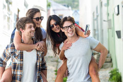 Hip men giving piggy back to their girlfriends and taking selfie Stock Images