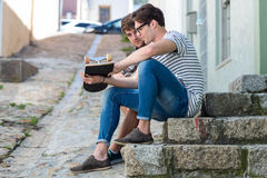 Hip men sitting on steps and holding skateboard Stock Photos